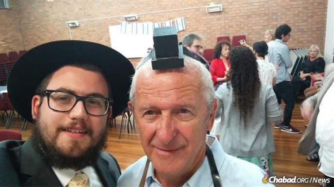 Rabbinical student Mendel Super, left, helps Joe Braun with tefillin.