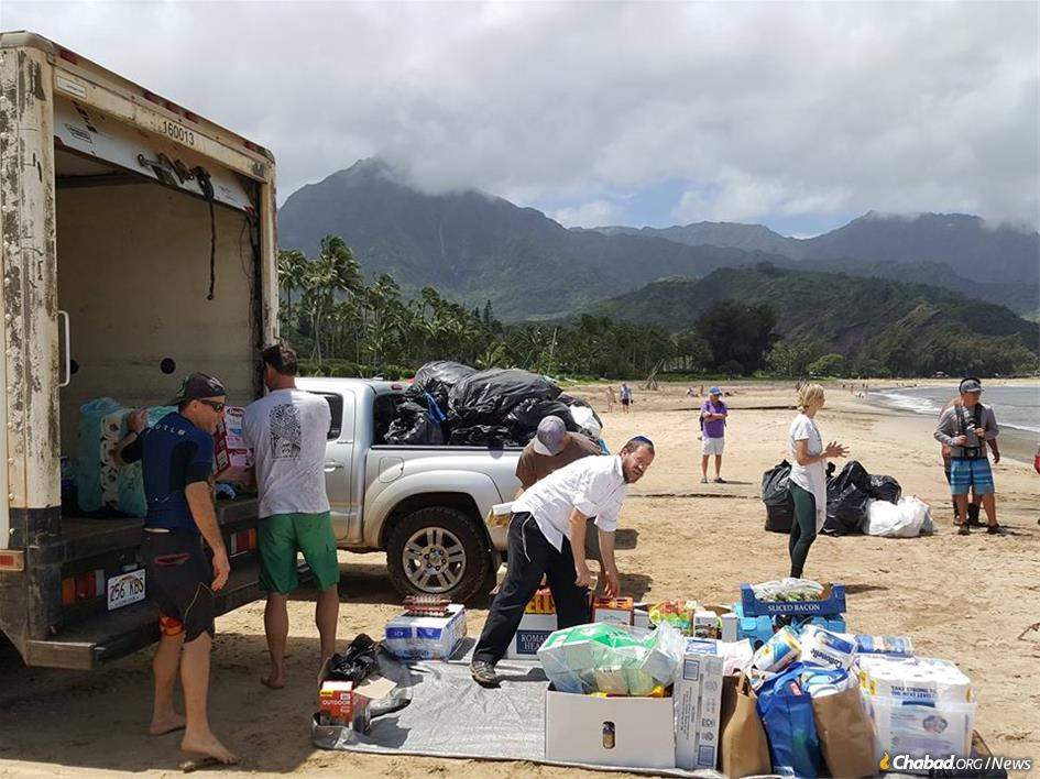 Rabbi Michoel Goldman unloads relief supplies on a beach in Kauai, Hawaii, to be ferried to families stranded inland by devastating floods.