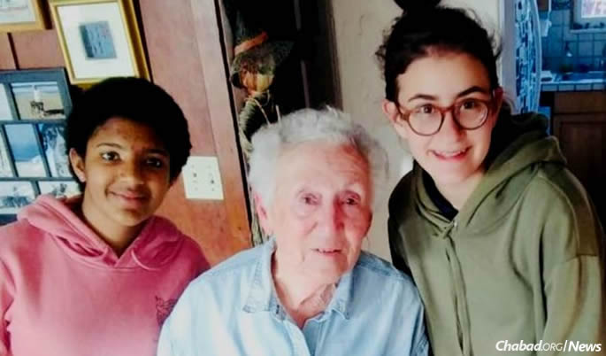 Holocaust survivor Lelah Hopps gratefully accepts challah from Eden Reese, left, and Chaya Muchnik.