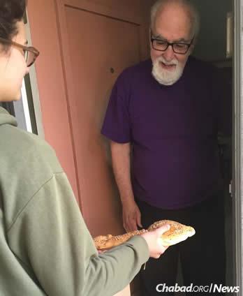 Sheldon Katz receives challah from Chaya Muchnik.