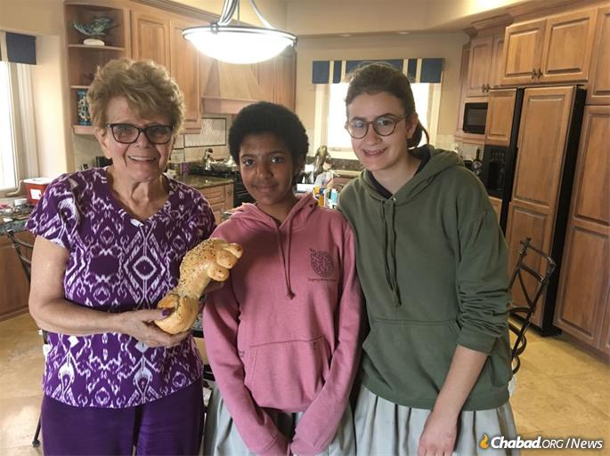 "Roz Resnick displays the ""key challah"" she received from Eden Reese and Chaya Muchnik."