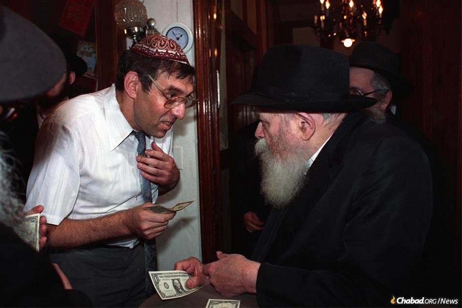 Dr. Yehoshua (Evsey) Neymotin receives a dollar and a blessing from the Rebbe. (Photo JEM/The Living Archive)