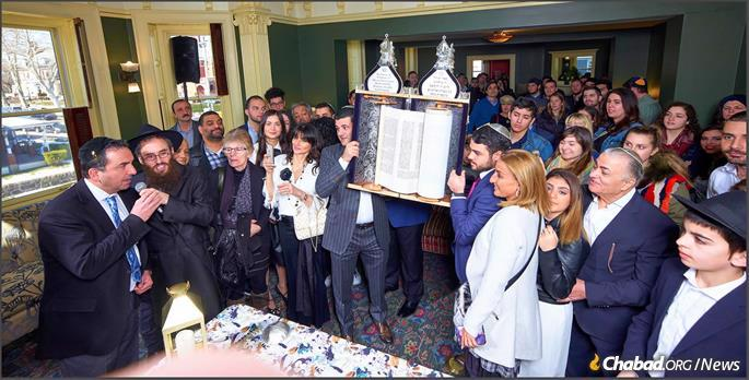 The Torah scroll arrives at its new home.