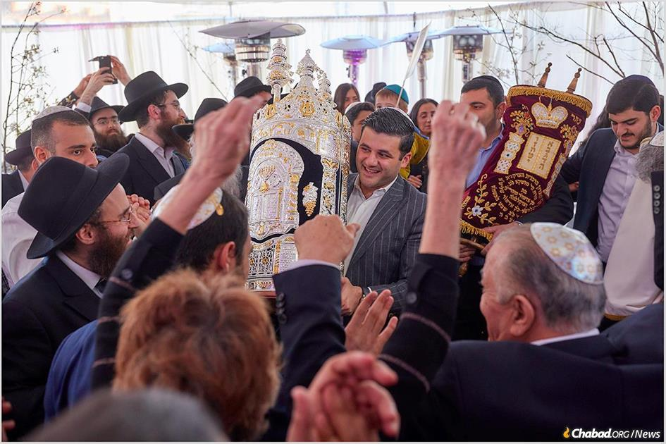 Rafael Ilishayev, center, dances with the Torah scroll that he and fellow almunus Yakir Gola dedicated to Chabad Serving Drexel University.