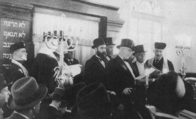 Mordechai Dubin being introduced in a synagogue, possibly during his 1929 visit to the United States. That year he accompanied the sixth Rebbe, Rabbi Yosef Y. Schneersohn, of righteous memory, on the Rebbe's trip to America. At the time, Dubin met with President Herbert Hoover and other American dignitaries, before leaving back to Latvia where he felt his voice was needed in the Saeima.