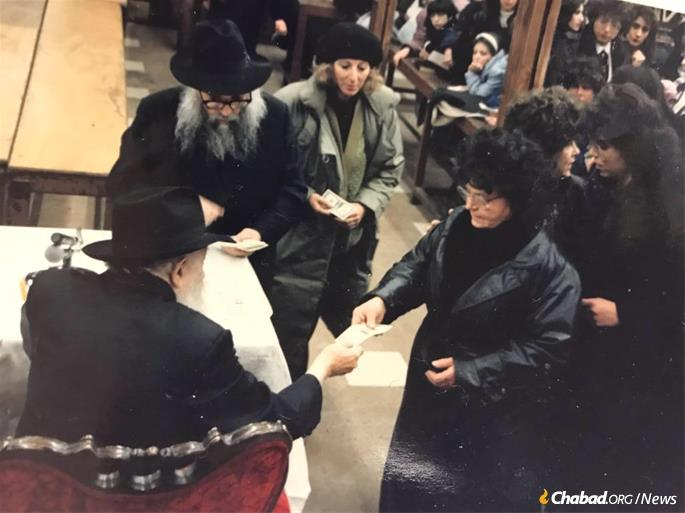 Receiving a dollar and a blessing from the Rebbe.