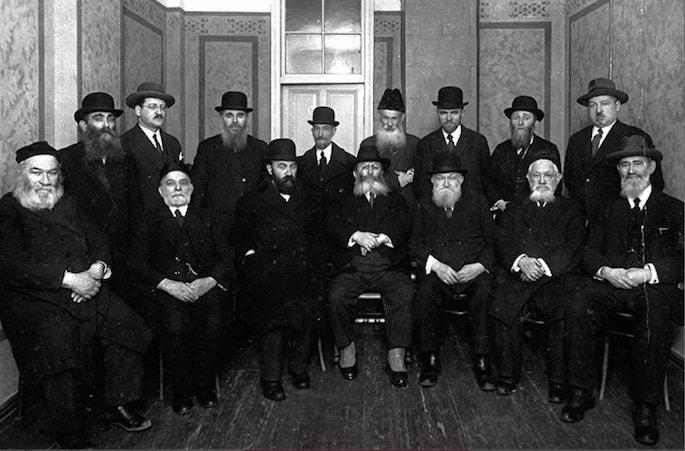 Group photo of the leaders of Agudas Yisroel of Latvia, circa 1930. Seated (R-L): Shalom Baf, Unknown, Mordechai Dubrovsky, Avigdor Volshonok, Mordechai Dubin, Zvi Hirsch Gutmann, Ben Zion Leibson. Photo: The Jews of Latvia/Association of Latvian and Estonian Jews in Israel.