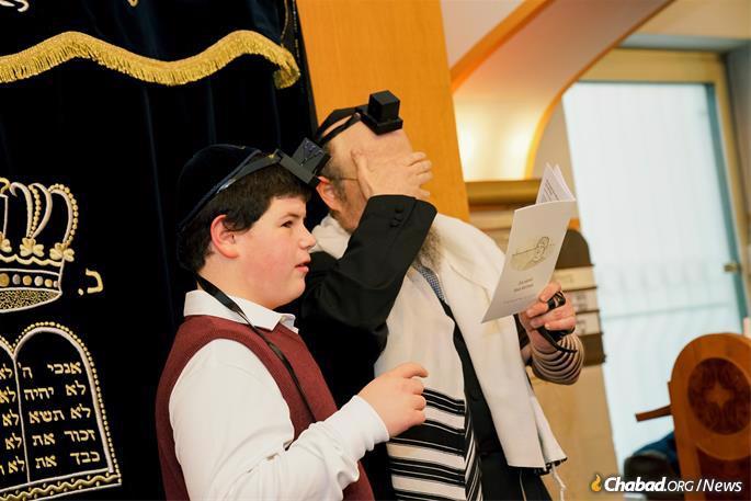 Father and son say the Shema Yisrael prayer.