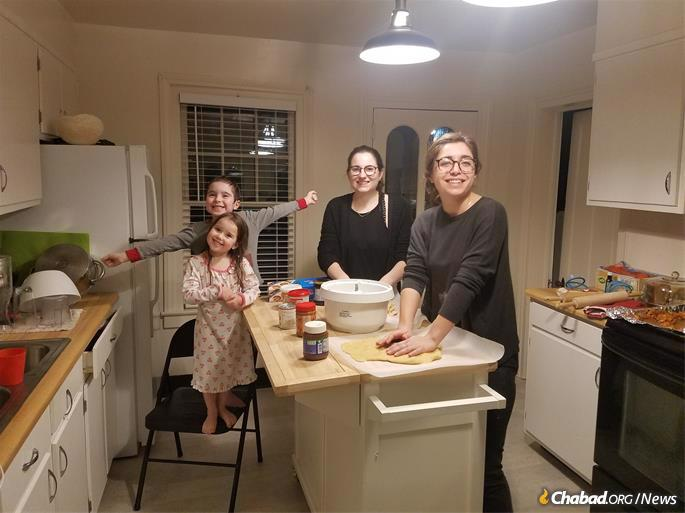 Ruthi Schmidt (far right) and Abby Tulchinsky prepare challah with Mendel and Yetta Waks.