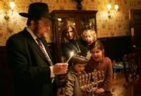 Rabbi Joshua Metzger, Shliach in Midtown Manhattan lights the Menorah with his family.