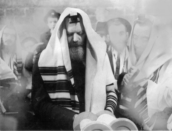 The Rebbe, wearing tallit and teffilin, makes a blessing on the Torah (mid 1960s).