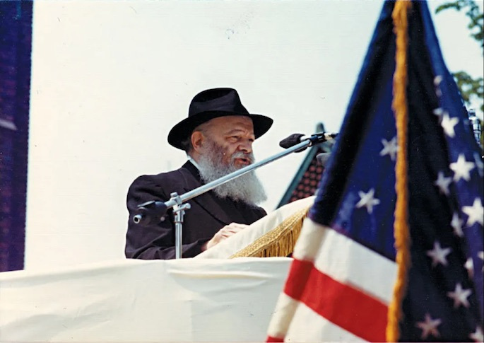 The Rebbe speaks to children at a Lag BaOmer parade in the mid 1970s. The flag of the United States of America is in the foreground.