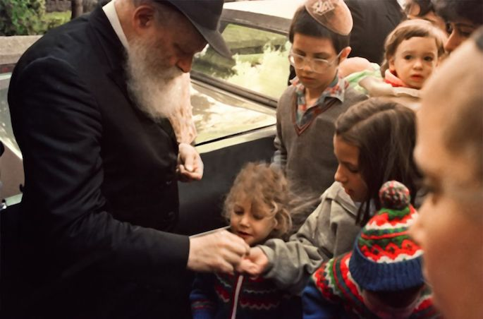 The Rebbe gives a young girl a coin so that she can donate it to charity (1980s).