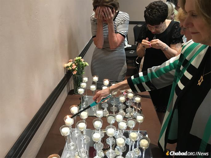 "Rhoda Morris, center, and others light Shabbat candles at ""Smile on Seniors"" event."