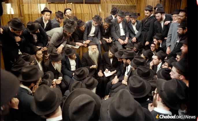 Chazarah, or repetition, following the Rebbe's farbrengen on Sept. 23, 1979. R' Yoel is in the center, elucidating a point, while to his right, taking notes, is Rabbi Dovid Feldman, today chief editor of Lahak. Chazzarah took place in the synagogue and was open to everyone. (Photo: JEM/The Living Archive)