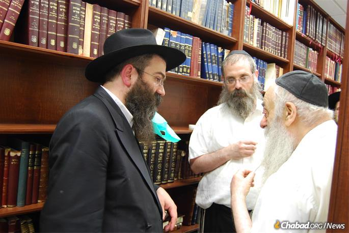 From left: Rabbi Chaim Shaul Brook, director of Lahak; Rabbi Dovid Feldman, its chief editor; and Rabbi Yoel Kahn, the Rebbe's chief chozer, in discussion at Lahak's office. (Photo: Lahak)
