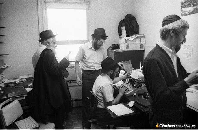 R' Yoel Kahn, left, can be seen reviewing notes of a farbrengen in an office at 770 in 1979. (Photo: JEM/The Living Archive)
