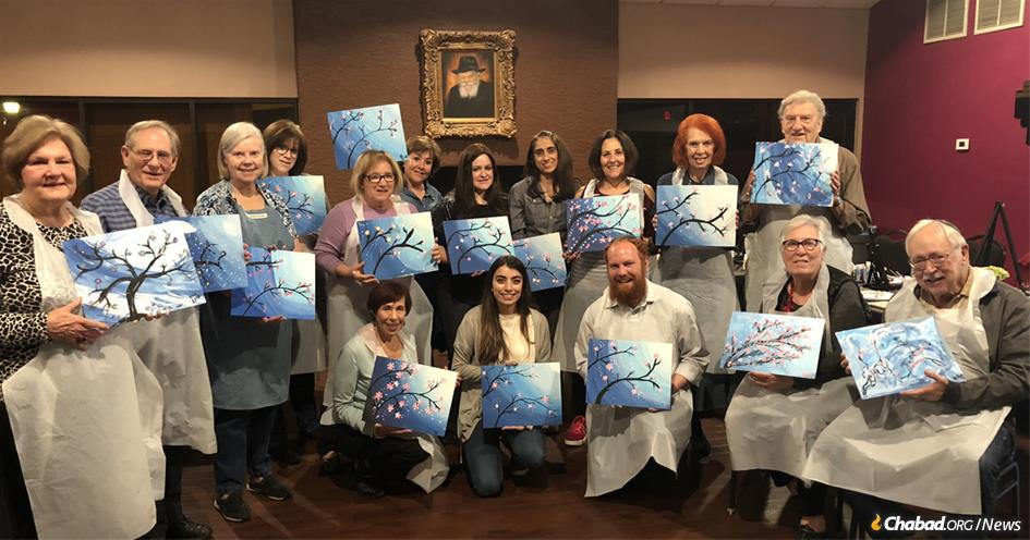 "Participants display their artwork at the ""Smile on Seniors"" program, part of Chabad of Downtown in Phoenix, co-directed by Rabbi Levi Levertov, bottom center, and Chani Levertov, top row, fifth from right."