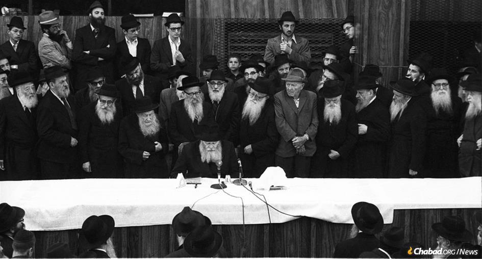 "The Rebbe recites a ""maamar,"" or Chassidic discourse, at a farbrengen gathering in the central Chabad synagogue at 770 Eastern Parkway in the Crown Heights neighborhood of Brooklyn, N.Y., on Sept. 4, 1975. While attendees mostly sat, the custom is to stand while the Rebbe teaches a discourse. The man wearing a hat in front of the Rebbe to his right is Rabbi Yoel Kahn, the Rebbe's chief chozer. (Photo: JEM/The Living Archive)"