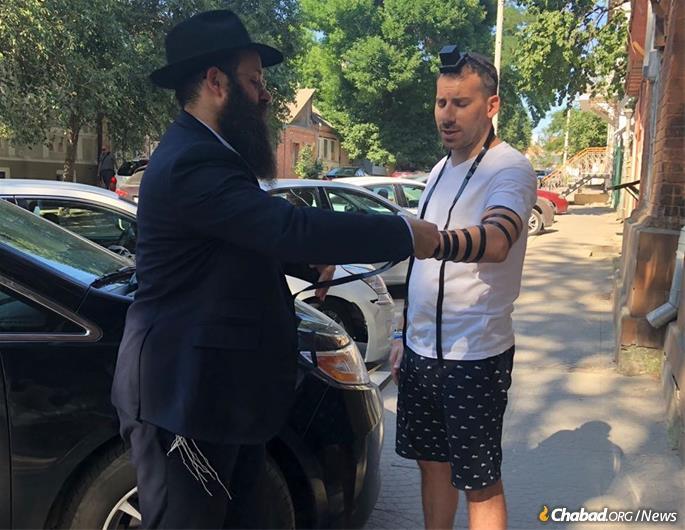 Rabbi Chaim Danzinger helps a tourist wrap tefillin and say Shema.