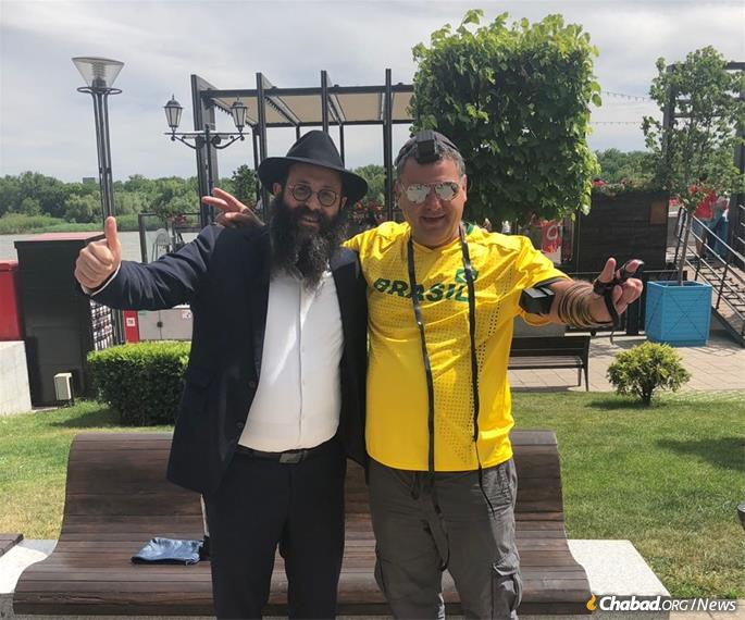 Rabbi Chaim Danzinger helps a happy tourist wrap tefillin and say Shema.