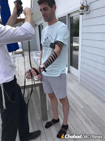 Banker Seth Binder wraps tefillin with Rabbi Aizik Baumgarten at Chabad of Montauk.