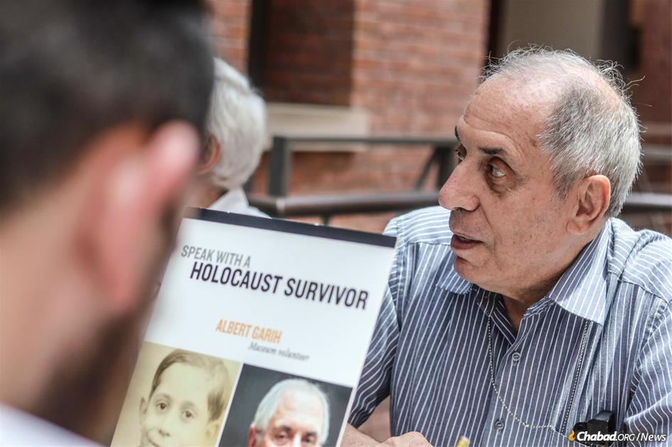 Holocaust museum volunteer Albert Garih speaks with a yeshivah student about his experiences as a survivor.