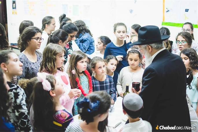 """Bassie Garelik remembers sitting on an educational panel in Milan when someone at the other end of the table piped up: """"The first time I experienced Shabbat was in Camp Gan Israel!"""" Here, Havdalah is recited at the end of Shabbat by Rabbi Avraham Hazan, Garelik's son-in-law, who ran the camp for many years. Today, it is directed by his son, Rabbi Levi Hazan. (Photo: Batsheva Helena Goldreich for Chabad.org)"""