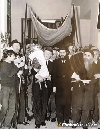 A Torah scroll welcomed to Chabad-Lubavitch of Milan, circa 1966. Rabbi Gershon Mendel Garelik is seen under the canopy, second from right. To his right holding a Torah scroll is R' Mendel Futerfas, the famed Chabad Chassid who spent nine years in the Soviet gulag and later became the head mentor at the Lubavitch yeshivah in Kfar Chabad, Israel.
