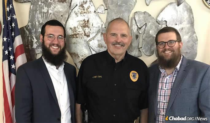 Wolf, left, with Whitefish police chief Bill Dial and Rabbi Chaim Bruk