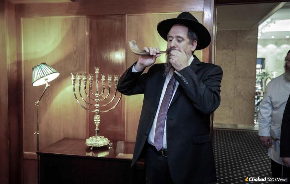 Rabbi Shaul Wilhelm blows the shofar at a ceremony in Oslo celebrating the permanent public display of a gold menorah in the Norway hotel where the Nobel Peace Prize is awarded each year. (Photo: Joseph Pessar)