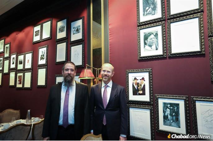 Wilhelm and Ben Philipson next to a photograph of the dedication of a new Torah scroll that took place at the hotel two years ago. (Photo: Joseph Pessar)