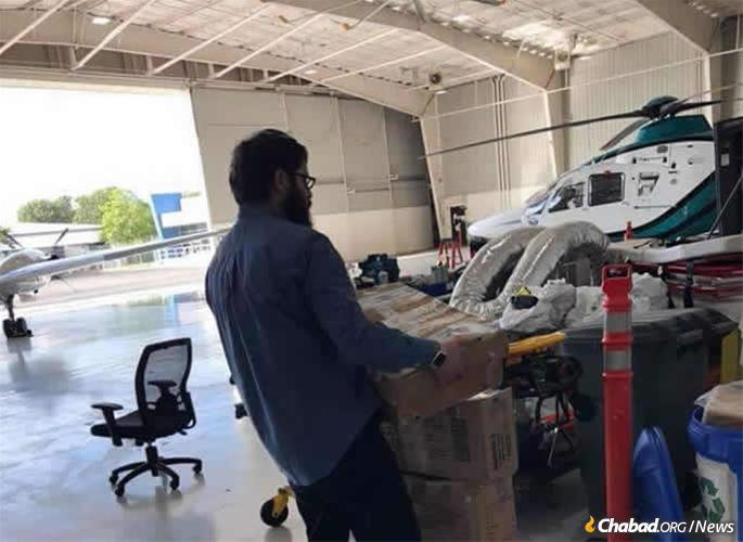 Rabbi Bentzion Groner prepares to load kosher food onto a waiting helicopter.