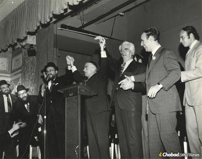 Taking on a leadership role in the Crown Heights Jewish community in the mid 1970s, he developed a warm relationship with Mayor Abe Beame. Fogelman, fourth from left, holds hands with Beame at a victory party in Crown Heights. (Photo: Fogelman family collection)