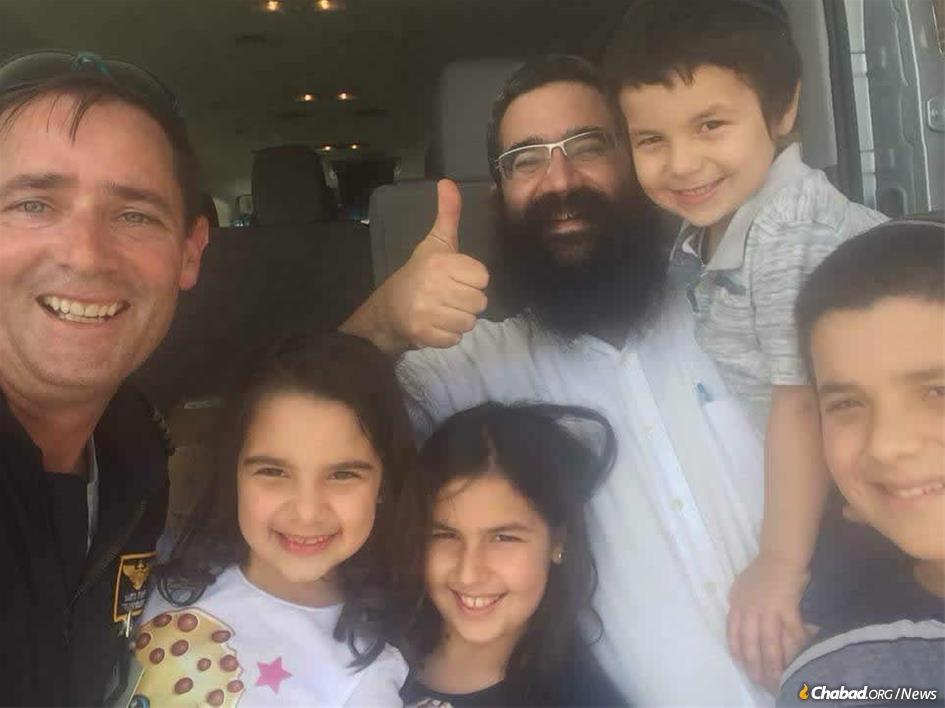 Rabbi Moshe Lieblich and children with the helicopter pilot who delivered much-needed supplies to Wilmington, N.C., just before Yom Kippur.
