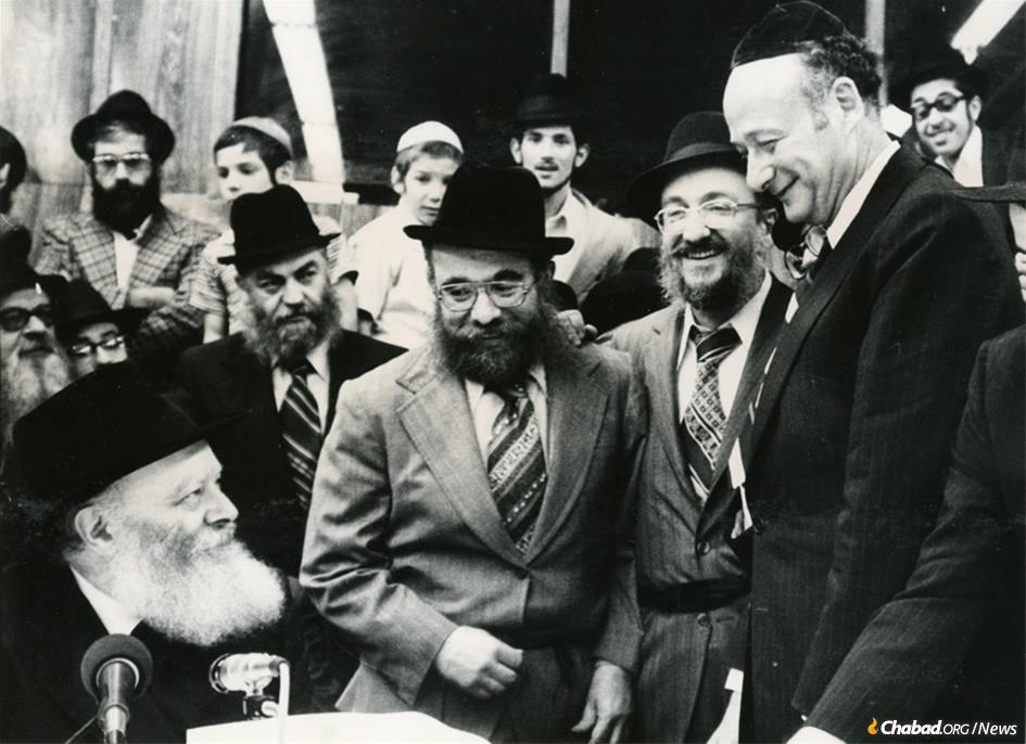 Rabbi Shmuel Eliyahu Fogelman, a longtime educator in Brooklyn, passed away on Aug. 30 at 88. For many years, he took an active role in community leadership as well, seen here (second from right) escorting then-Mayor Ed Koch (far right) to the Rebbe—Rabbi Menachem M. Schneerson, of righteous memory—at a farbrengen gathering at 770 Eastern Parkway in Brooklyn. (Photo: Fogelman family collection)