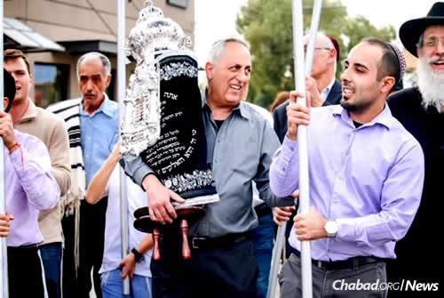 Des hommes juifs dansant avec une Torah nouvellement écrite. À cette occasion, la communauté effectue une marche symbolique vers la synagogue pour y accueillir cette Torah avec profusion de joie et de chants.