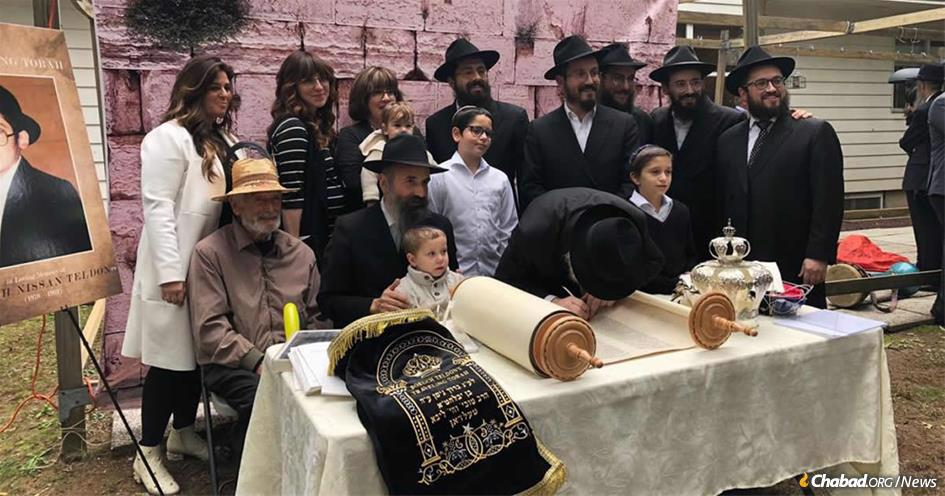 Rabbi Tuvia and Chaya Teldon, and family, at the completion of a Torah scroll dedicated to the memory of Boruch Teldon, who passed away 27 years ago at the age of 13 from complications related to cystic fibrosis.