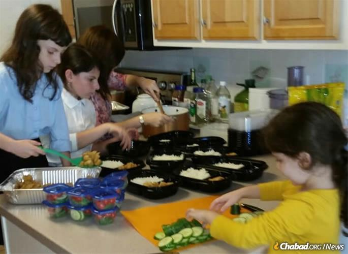 The Tenenboim family prepares meals for hurricane victims.