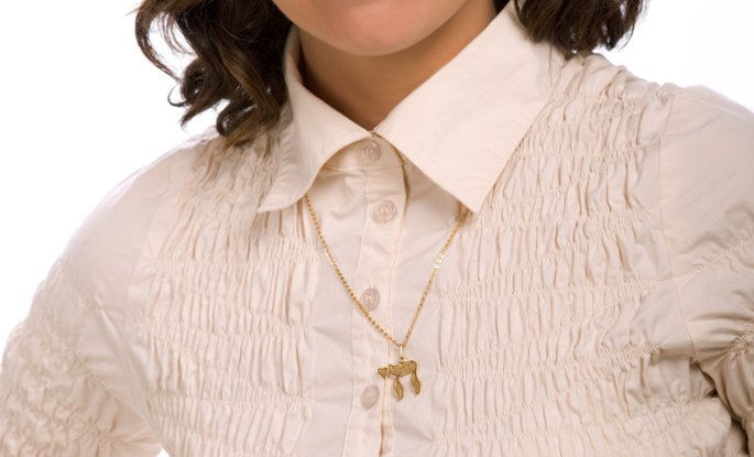 A chai pendant worn by a woman.