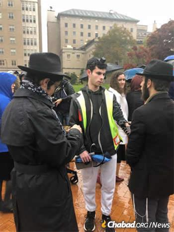 Students of Yeshiva Schools of Pittsburgh help someone pray in tefillin at Sunday evening's vigil at Soldiers and Sailors Memorial Hall in Pittsburgh.