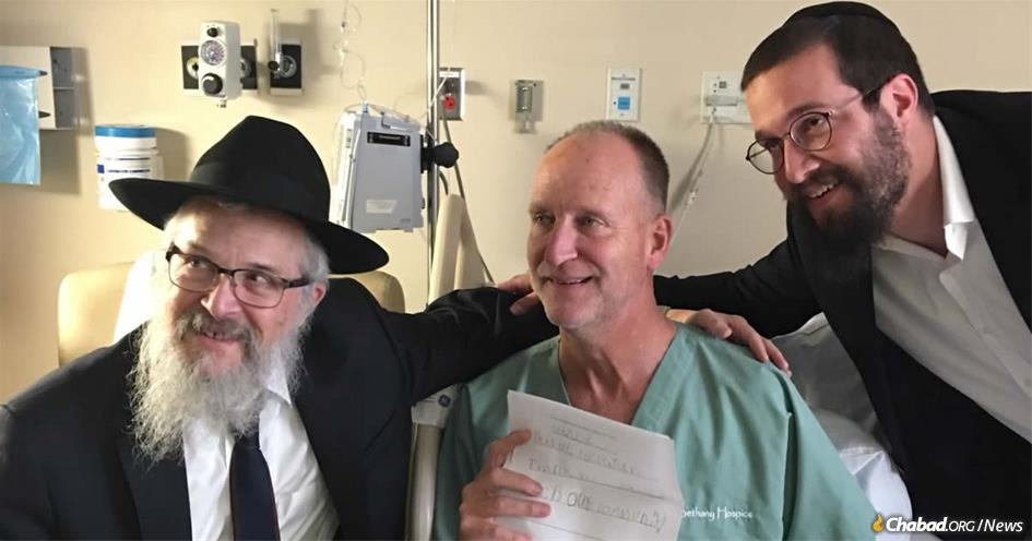 Officer Dan Mead, center, holds a letter of thanks from second-grade students at Yeshiva Schools of Pittsburgh. He is flanked by Rabbi Yisroel Rosenfeld, left, and Rabbi Henoch Rosenfeld.