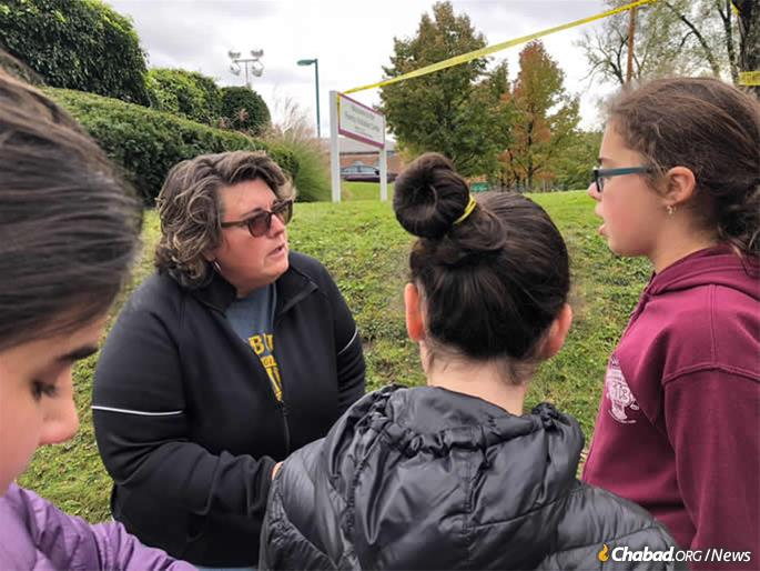 Yeshiva girls have also been distributing Shabbat candles and Good Cards, asking people to do something kind for another, pictured here outside of Tree of Life.