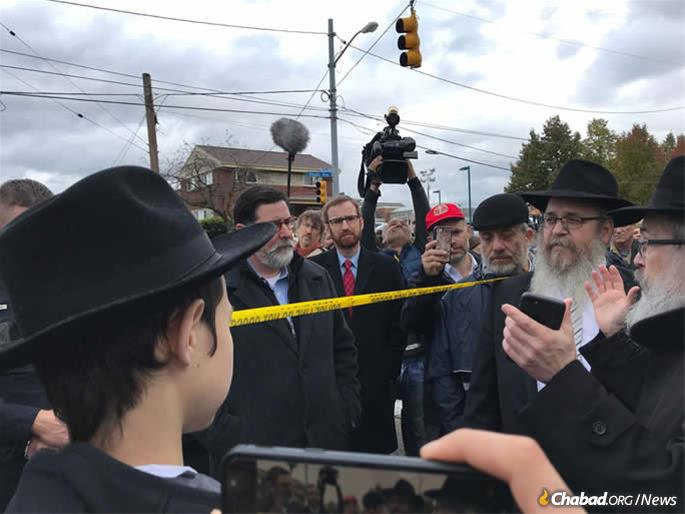 Rabbi Yisroel Rosenfeld (right), director of Chabad of Western Pennsylvania, speaks at a minchah prayer on Monday afternoon outside of Tree of Life, as Pittsburgh Mayor Bill Peduto looks on.