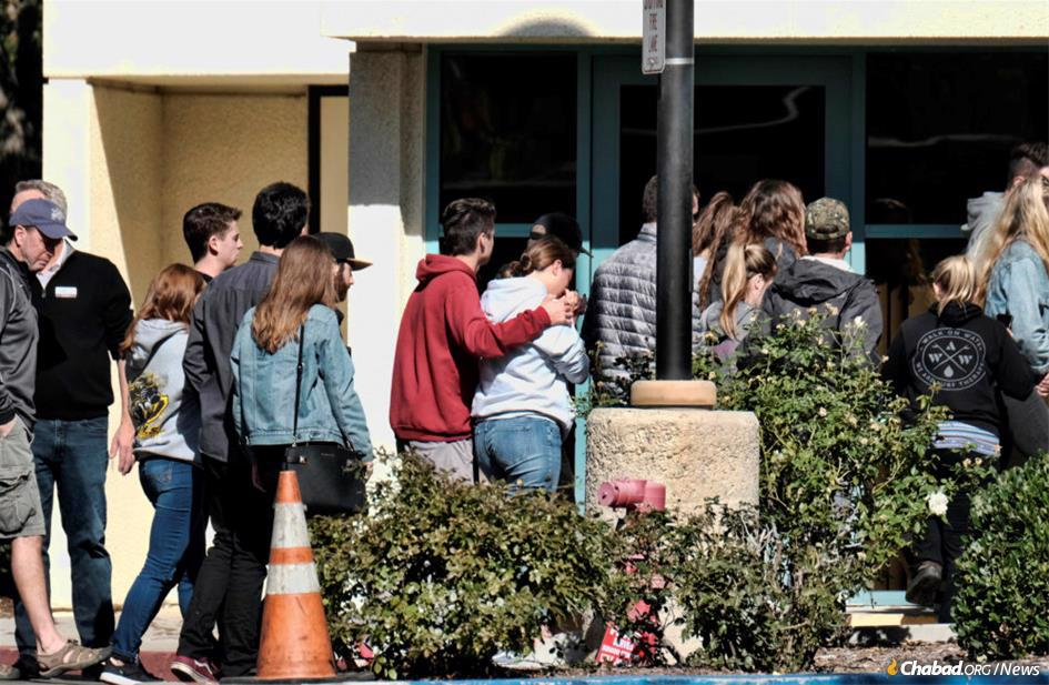 Families gather at the Thousand Oaks Teen Center to await news of their loved ones. (Photo: NPR)