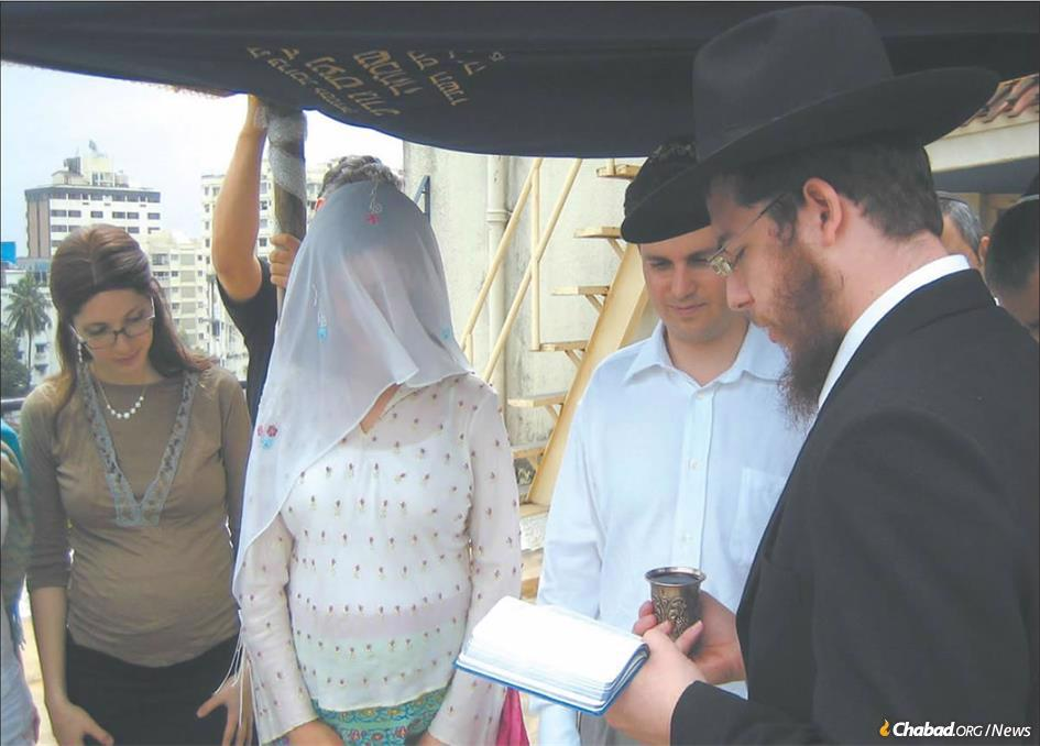 Rabbi Gavriel Holtzberg (right) officiates at a wedding in Mumbai as his wife, Rivka (left) looks on. The Holtzbergs, the founders and directors of Chabad-Lubavitch of Mumbai, were killed along with four guests during a brutal attack on their center 10 years ago. (Photo: Chabad.org)