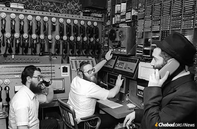 Rabbi Yosef Yitzchak Kazen, center, at at WLCC, Chabad's telephone communications hub.