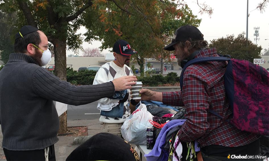 Rabbi Mendy Zwiebel, left, is out on the streets of Chico, Calif., often with his family, helping those who were devastated by fire. Residents are encouraged to wear masks due to pollution from ash that is everywhere, though not everyone has been complying with the suggestion.