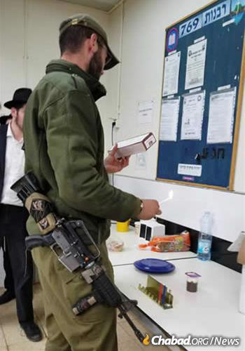A soldier recites the blessing over the Chanukah menorah.