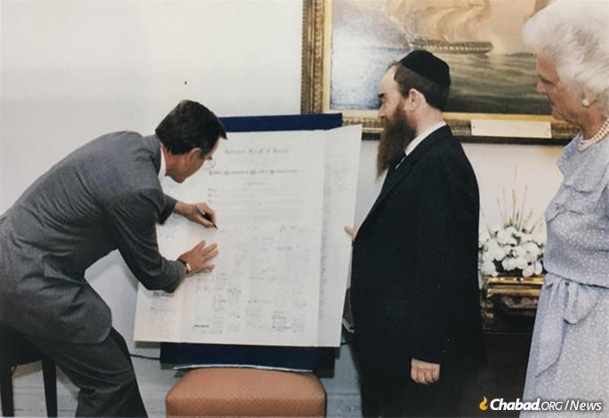 Then-Vice President George Bush signs the National Scroll of Honor for the Rebbe's 80th birthday in 1983, as Rabbi Abraham Shemtov, national director of American Friends of Lubavitch (Chabad), and the vice president's wife, Barbara Bush, look on.